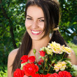 Girl smiling holding a vase with a bouquet of red and yellow roses on a hot summer day. — Stock Photo