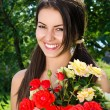 Girl smiling holding a vase with a bouquet of red and yellow roses on a hot summer day. — Stock Photo #42818477