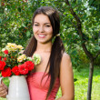 Girl smiling holding a vase with a bouquet of red and yellow roses on a hot summer day. — Stock Photo #42818479