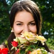 Girl smelling a bouquet of red and yellow roses on a hot summer day. — Stock Photo #42818485