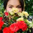 Girl smelling a bouquet of red and yellow roses on a hot summer day. — Stock Photo #42818487