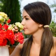 Girl smelling a bouquet of red and yellow roses on a hot summer day. — Stock Photo #42818495