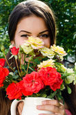 Girl smelling a bouquet of red and yellow roses on a hot summer day. — Stok fotoğraf