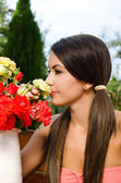 Girl smelling a bouquet of red and yellow roses on a hot summer day. — Stock Photo