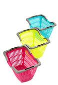 Niebieski, żółty i różowy plastikowe zakupy koszyka na białym tle. — Zdjęcie stockowe