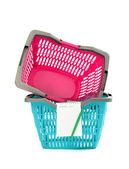 Blue and pink plastic shopping basket with blank shopping list isolated on white. — Stock Photo