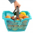 Man hand carrying a shopping basket full of groceries. — Stock Photo