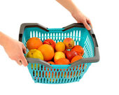 Woman hands carrying a shopping basket full of fruits. — Stock Photo