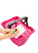 Woman hand writing the shopping list and a pink market basket. — Stock Photo
