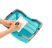 Woman hand writing the shopping list and a blue market basket. — Stock Photo
