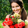 Beautiful woman in the garden with flowers. — Stock Photo