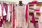 Dressing closet with pink clothes arranged on hangers and shelf. — Stock Photo