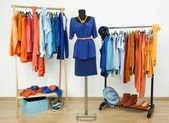 Dressing closet with complementary colors blue and orange clothes arranged on hangers and an outfit on a mannequin. — Stock Photo