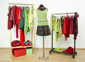 Dressing closet with complementary colors red and green clothes arranged on hangers and an outfit on a mannequin. — Stock Photo