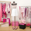Dressing closet with pink clothes arranged on hangers and an outfit on a mannequin. — Stock Photo #45573041