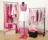 Dressing closet with pink clothes arranged on hangers and an outfit on a mannequin. — Stock Photo