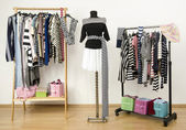 Dressing closet with striped clothes arranged on hangers. Black and white outfit on a mannequin. — Stock Photo