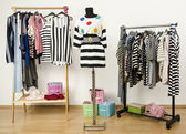 Dressing closet with striped clothes arranged on hangers. Outfit with stripes and polka dots on a mannequin. — Stock Photo