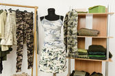 Dressing closet with military camouflage khaki green clothes arranged on hangers and shelf, outfit on a mannequin. — Stock Photo