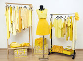Dressing closet with yellow clothes arranged on hangers and an outfit on a mannequin. — Stock Photo