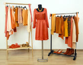 Wardrobe with orange clothes arranged on hangers and a dress on a mannequin. — Stock Photo