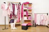 Dressing closet with pink clothes arranged on hangers and shelf, outfit on a mannequin. — Stock Photo