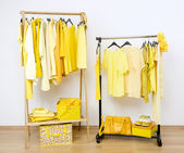 Dressing closet with yellow clothes arranged on hangers. — Stock Photo