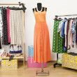 Постер, плакат: Dressing closet with polka dots clothes arranged on hangers and an orange outfit on a mannequin