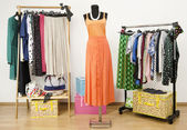 Dressing closet with polka dots clothes arranged on hangers and an orange outfit on a mannequin. — Stock Photo