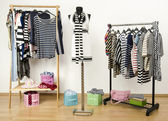 Dressing closet with striped clothes arranged on hangers. — Stock Photo
