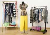 Dressing closet with striped clothes arranged on hangers and an outfit on a mannequin. — Stock Photo