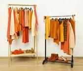 Dressing closet with orange clothes arranged on hangers. — Stock Photo