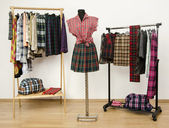 Dressing closet with plaid clothes arranged on hangers and an outfit on a mannequin. — Stock Photo