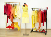 Wardrobe with yellow, orange and red clothes arranged on hangers and a yellow outfit on a mannequin. — Stock Photo