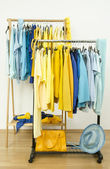 Dressing closet with shades of yellow and blue clothes hanging on a rack nicely arranged. — Stock Photo