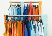 Close up on complementary colors clothes on hangers in a store. — Stock Photo