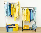 Wardrobe with shades of yellow and blue clothes hanging on a rack nicely arranged. — Stock Photo