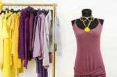 Dressing closet with complementary colors violet and yellow clothes. — Stock Photo