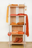 Orange clothes nicely arranged on a shelf. — Stock Photo
