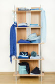 Blue clothes nicely arranged on a shelf. — Stock Photo