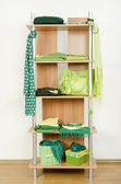 Green clothes nicely arranged on a shelf. — Stock Photo