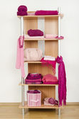 Pink clothes nicely arranged on a shelf. — Stock Photo