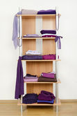 Purple clothes nicely arranged on a shelf. — Stock Photo
