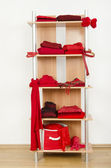 Red clothes nicely arranged on a shelf. — Stock Photo