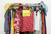Cute summer outfits displayed on hangers with a big sale sign. — Stock Photo