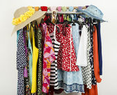 Cute summer outfits and wicker hats on a rack. — Stock Photo