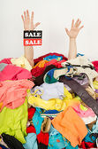 Man hands with the sale sign reaching out from a big pile of clothes and accessories. — Stock Photo