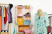 Wardrobe with summer clothes nicely arranged and a beach outfit on a mannequin. — Stock Photo