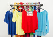 Cute red, yellow, blue blouses displayed on hangers with the sale sign. — Stock Photo
