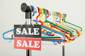Close up on empty hangers and a big sale sign. — Stock Photo